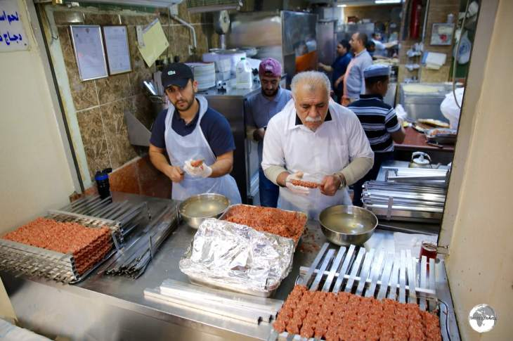 Two chefs preparing Kofte shish kebabs at Souk Al-Mubarakiya.