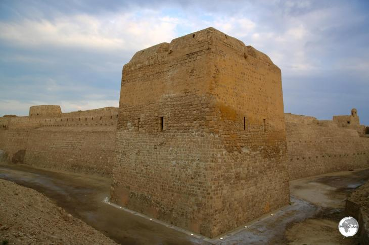 The exterior view of Bahrain fort at dusk.