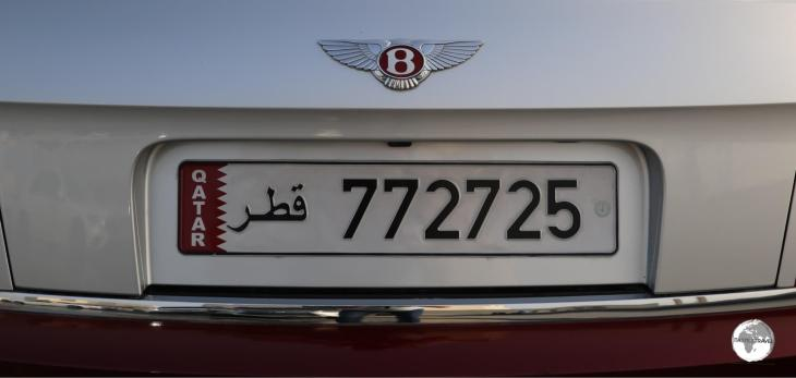 A Bentley logo in Qatari purple. All Qatari license plates feature the national flag.
