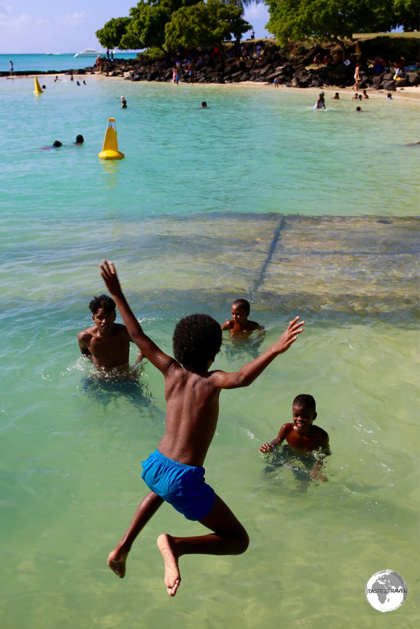 Young Mauritians enjoying the beach at Grand Baie.