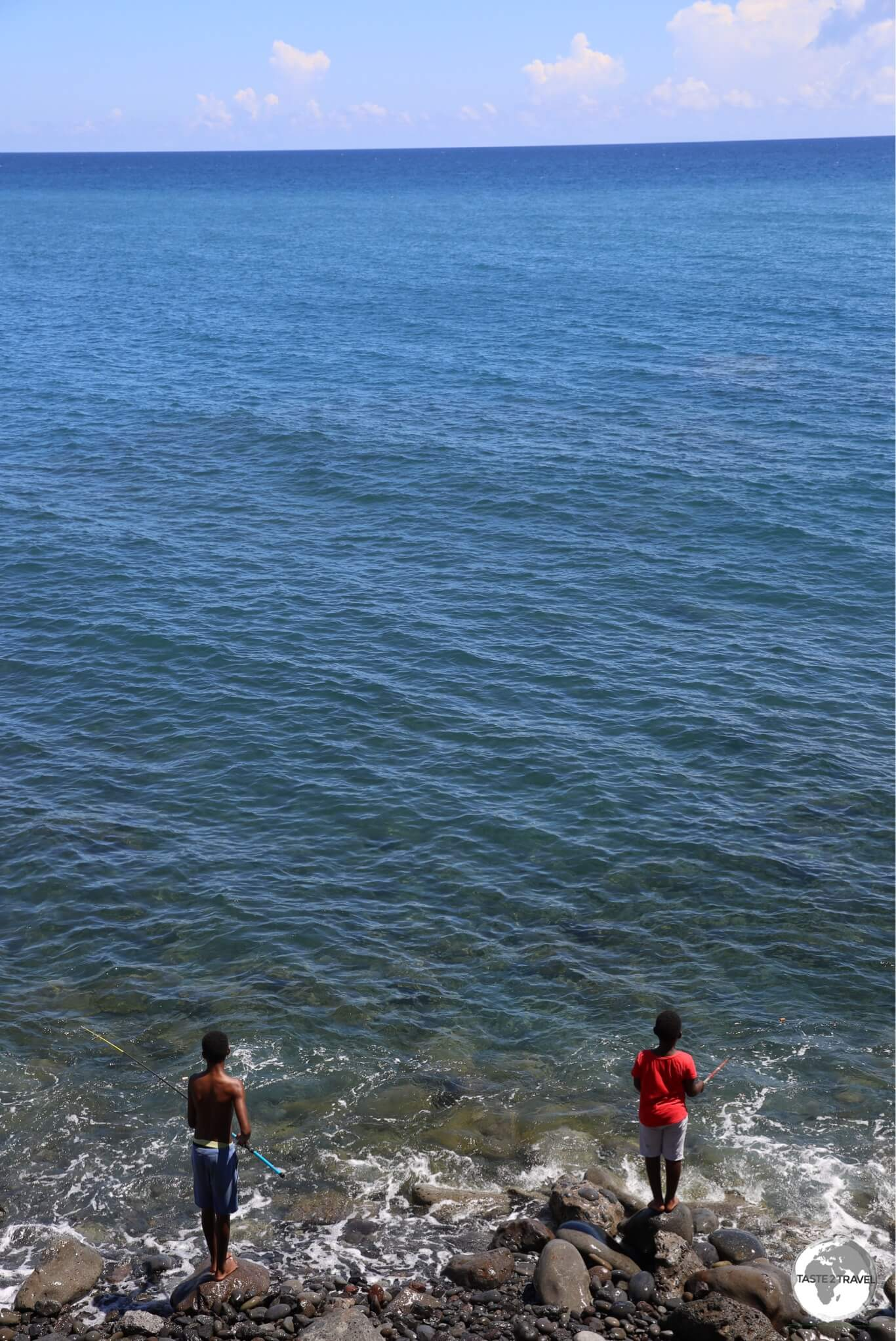 The clean waters of the Indian ocean provide an ideal fishing ground for two local boys, seen here at Le Barachois.