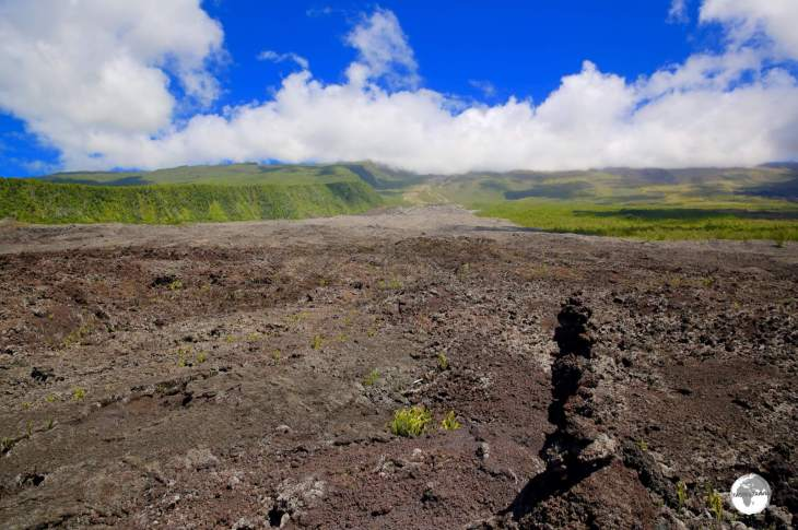 One of many huge lava fields which flow down to the south coast of Reunion from the Piton de la Fournaise, which is shrouded by cloud cover.