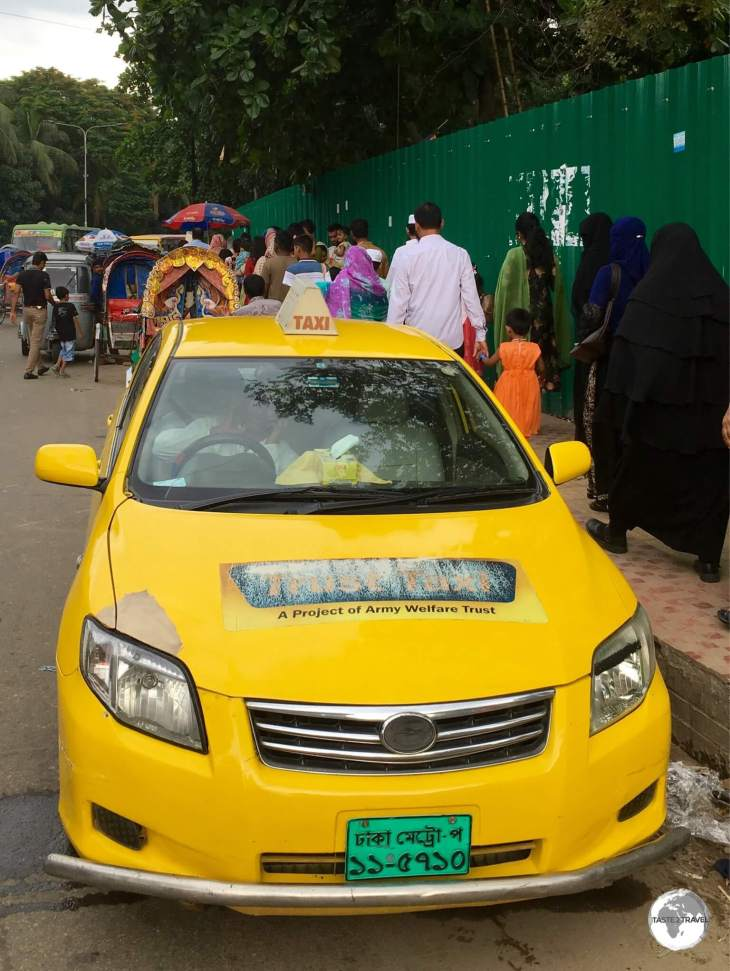 Taxis in Dhaka are well out-numbered by the more numerous rickshaws.