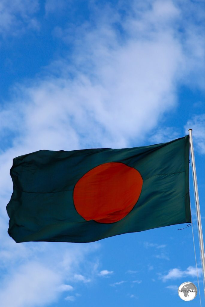 The flag of Bangladesh flying at the Eternal Flame monument.