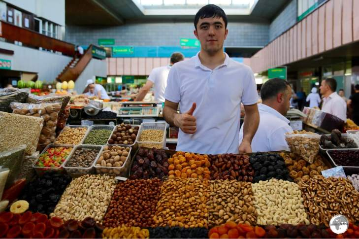 A vendor at the Green Bazaar selling dried fruits and nuts at bargain prices.