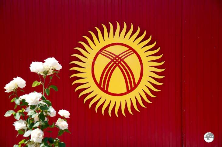 This Kyrgyzstan flag adorns the wall of a colourful house in the town of Karakol.
