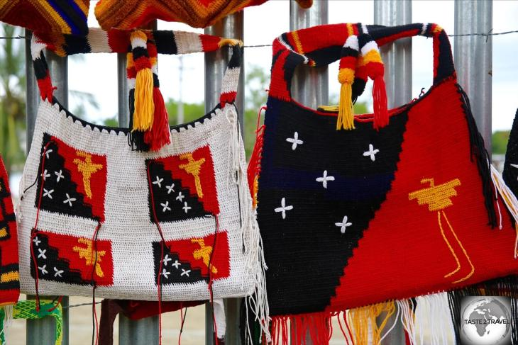 The flag of PNG is often featured on local crafts, such as these handwoven <i> bilums </i> on sale in Madang market.
