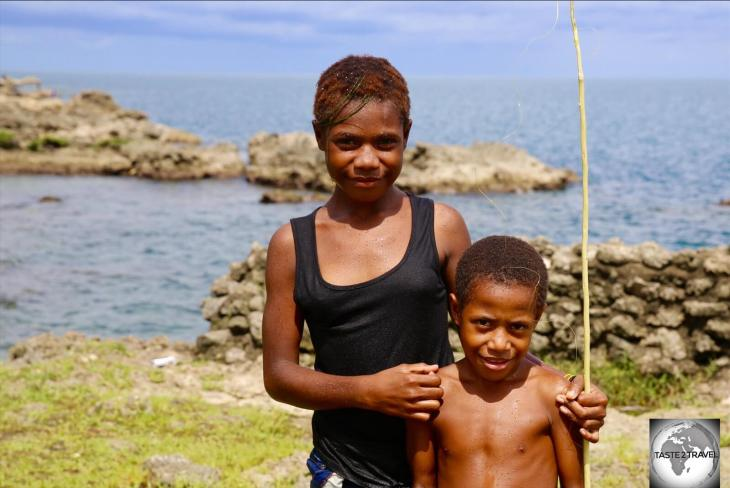 A sister, with her brother, at Machine Gun beach in Madang.