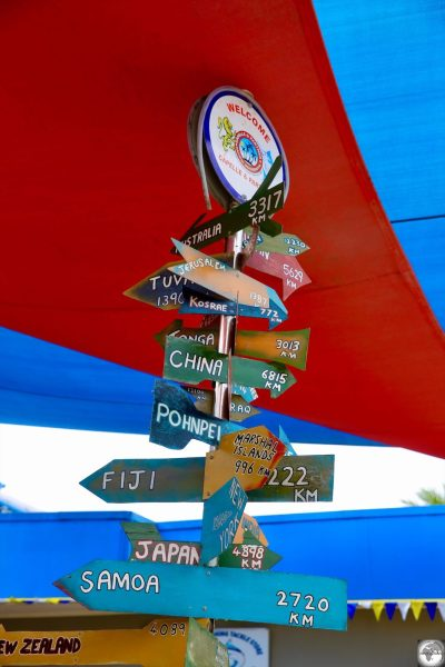 A signboard outside of the Capelle and Partner supermarket indicates distances to different countries from Nauru.