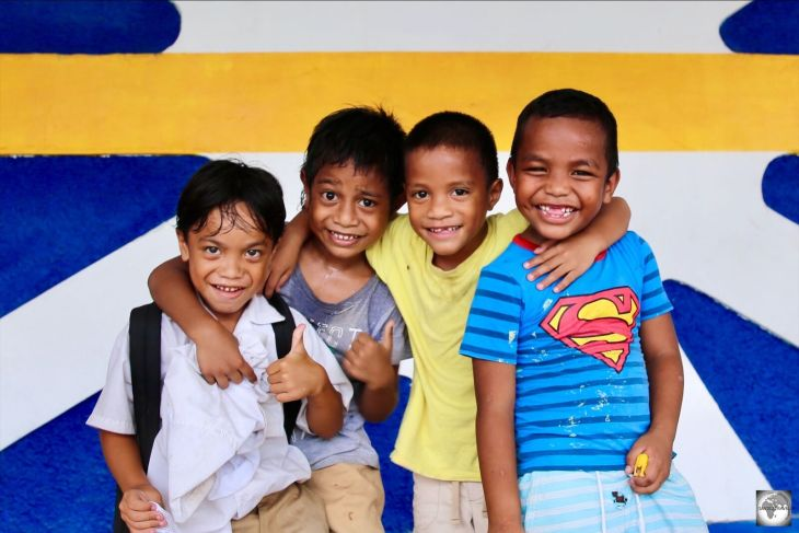 Boys posing in front of a giant flag of Nauru which adorns the wall of the Civic centre.