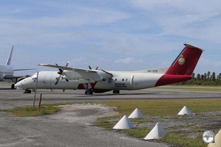 A Dash-8 surveillance plane, operated by Australian Border Force, parked on the runway at Cocos (Keeling) Airport.