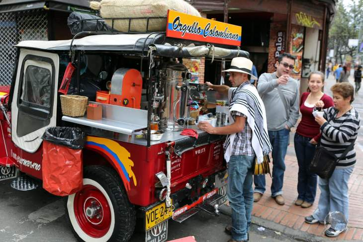 A coffee vendor, selling freshly brewed Colombian coffee from the back of his 'Willys' jeep in downtown Bogota.