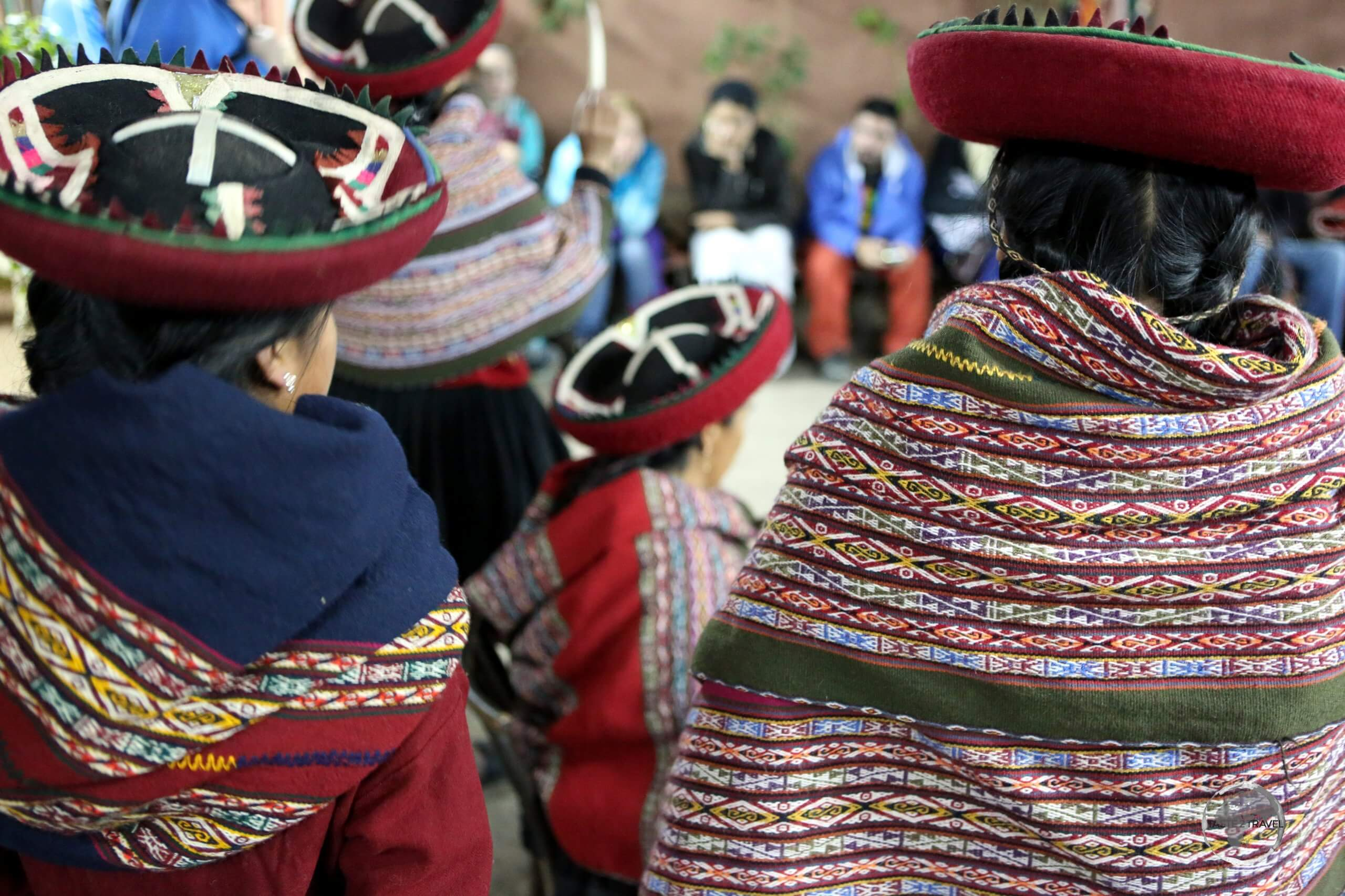 Quechua weavers at the 'Chinchero Centre for Traditional Culture', wearing their woven garments, which they sell to visiting tourists.