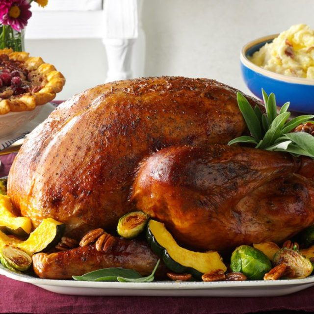 Roasted turkey on a platter surrounded by vegetables