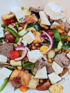 Greek panzanella salad. White bowl filled with Cedar's tzatziki sauce, cut red orange & yellow cherry tomatoes, chopped red onions, medium diced cucumber, roasted chickpeas, green pepper slices, chunks of feta cheese, lamb and beef gyro meat and toasted pita
