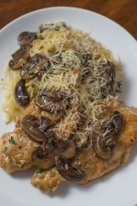 White plate with chicken marsala, mushrooms, linguine, and freshly grated parmesan