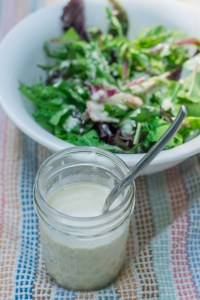 mason jar with garlic tahini salad dressing and spoon sitting on a colorful kitchen towel in front of a bowl of lettuce covered in the dressing