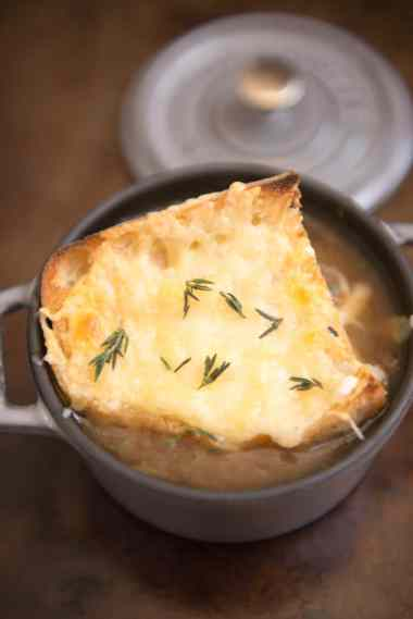 gray staub mini cocotte filled with french onion soup and topped with crusty bread and melted bubbly cheese and fresh thyme