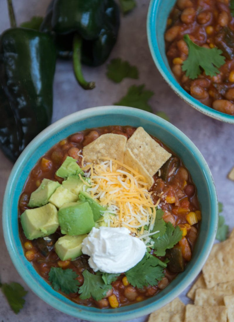 two blue bowls full of hearty southwestern vegetarian chili, one topped with tortilla strips, shredded cheese, cubed avocado, cilantro and sour cream + chips and poblano peppers on a gray backdrop
