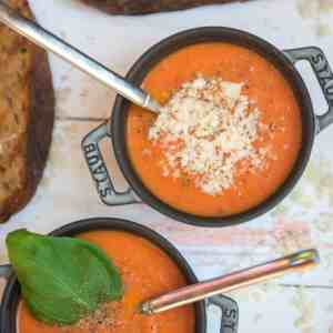 tomato soup in gray Staub cocottes with freshly grated parmesan, black pepper and basil