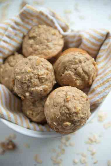 white bowl full of healthy banana oat muffins with white and yellow striped kitchen towel