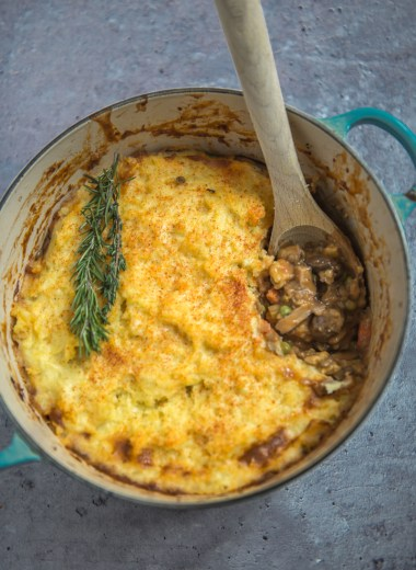 Vegetarian Shepherd's Pie in a blue Dutch oven with a wooden spoon
