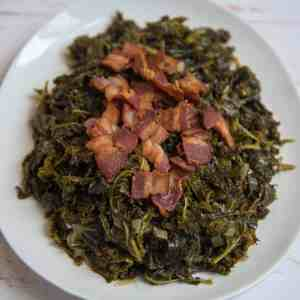 white plate full of southern style mustard greens topped with crispy bacon