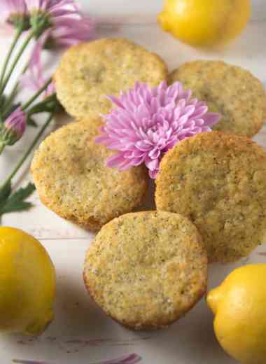 lemon poppy seed muffins with lemons and a purple flour in the center