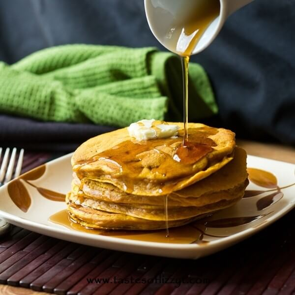 pouring maple syrup over protein pumpkin pancakes