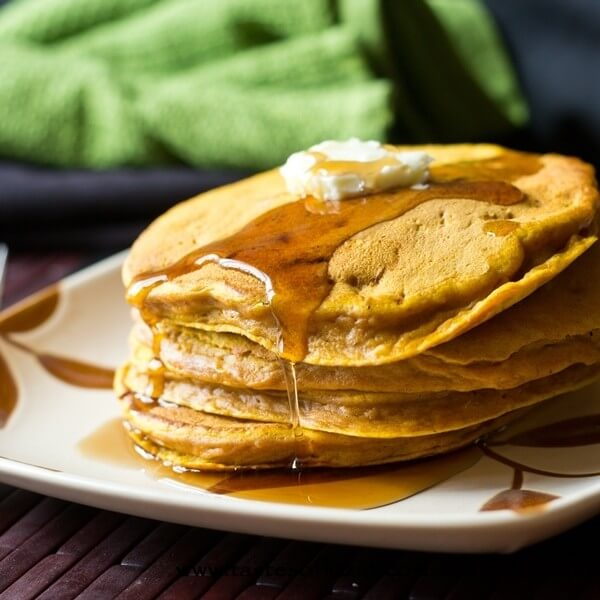 stack of homemade pumpkin pancakes with syrup