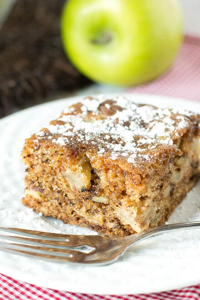 slice of apple walnut cake on a plate with a fork