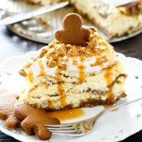 Thick, rich gingerbread cheesecake layered with gingerbread loaf batter. Spiced whipped topping, crushed ginger snaps and caramel top this decadent, holiday dessert!