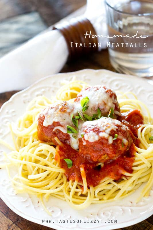 white dinner plate with homemade Italian meatballs and tomato sauce on a bed of spaghetti