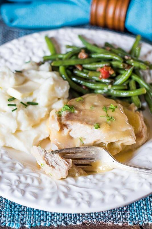 tender pork chops and gravy on a plate with homemade mashed potatoes and green beans