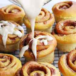 Pumpkin spice cinnamon buns being drizzled with icing