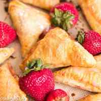 Quick and easy strawberry turnovers made with puff pastry and stuffed with fresh strawberry filling. Drizzle with glaze for a beautiful spring brunch recipe.