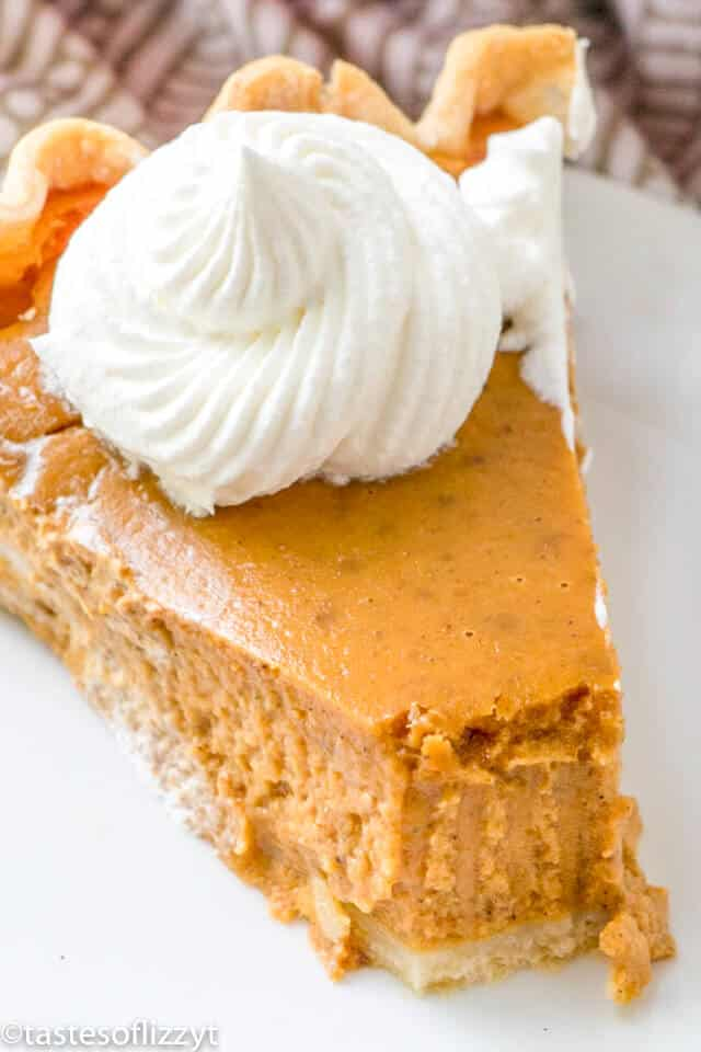 slice of the best pumpkin pie topped with a dollop of whipped cream