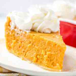a slice of sweet potato pie topped with whipped cream