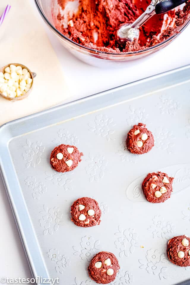 scoops of red velvet cookie dough on a baking sheet