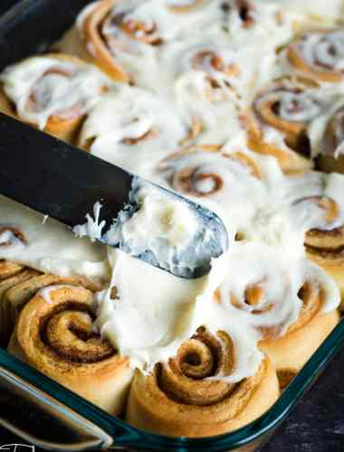 spreading cream cheese frosting on cinnamon rolls