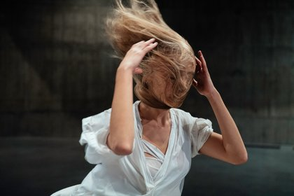figure with hands either side of their head and long blonde hair blowing across their face.