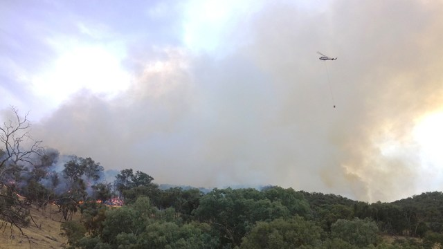 A water-bombing helicopter assists firefighters at the Minjary blaze.