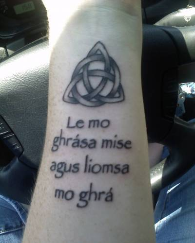 Gaelic symbol tattoo on man's forearm. The phrase, Cairdeas, Dilseacht,