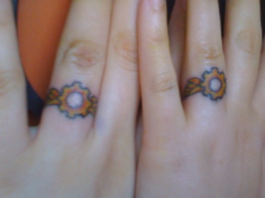 Yellow Ring Tattoo On Fingers