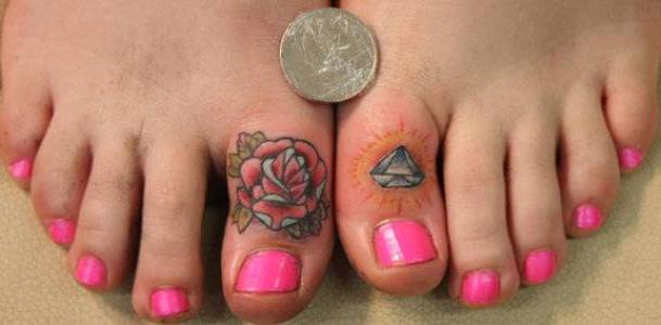 Tattoos on the fingers of the girl - rose and diamond