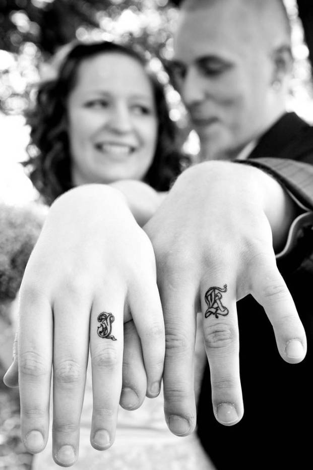 Tattoos on the ring fingers of the girl and the guy - initials