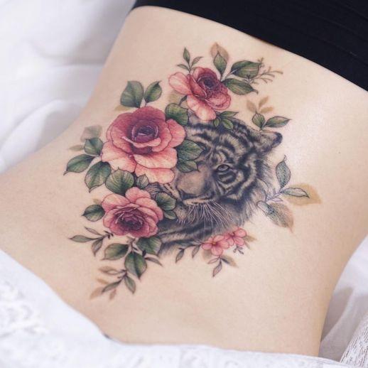 Tigre asomado entre flores rosas por Tattooist Silo
