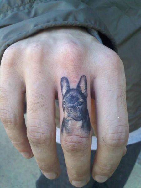 tattoo de un perro en el dedo