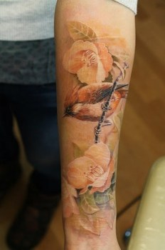 realistic bird tattoo on arm