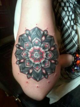 Mándala tatuada en brazo